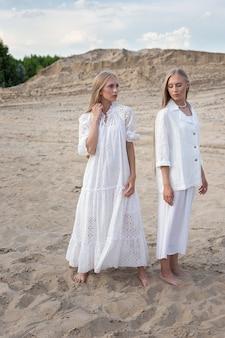Dwie atrakcyjne młode siostry bliźniaczki pozowanie w kamieniołomie w eleganckie białe ubrania