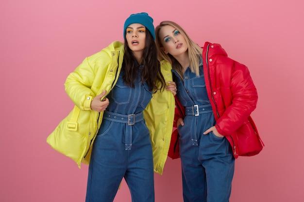 Dwie atrakcyjne stylowe kobiety pozujące na różowej ścianie w kolorowej zimowej kurtce puchowej w kolorze czerwonym i żółtym, trend w modzie na ciepłe ubrania