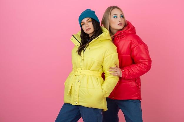 Dwie atrakcyjne stylowe kobiety pozujące na różowym tle w kolorowej zimowej kurtce puchowej w kolorze czerwonym i żółtym, trend w modzie na ciepłe ubrania