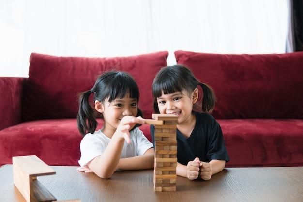 Dwie azjatki bawiące się drewnianymi stosami w domu