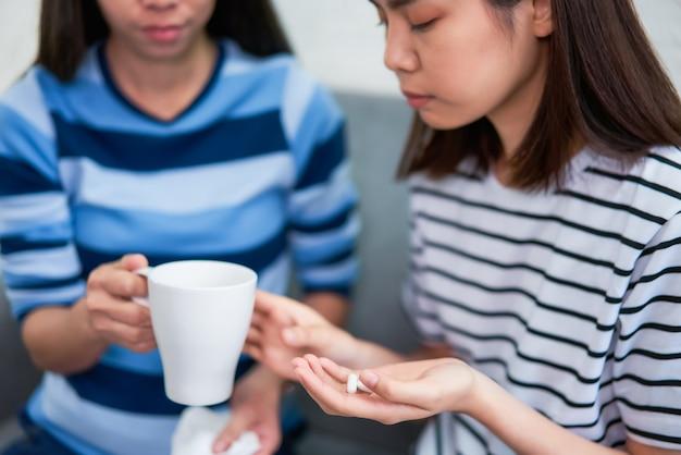 Dwie azjatki biorące do ust białą pigułkę i pijące wodę w szklance na kanapie w domu, czują się jak chore. pojęcie opieki zdrowotnej.