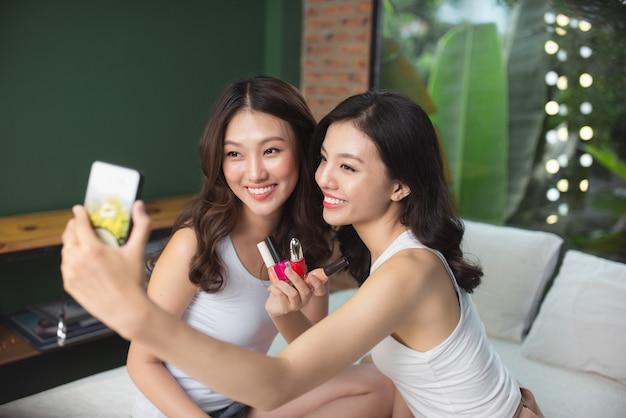 Dwie azjatki malują paznokcie u rąk i nóg na łóżku w salonie