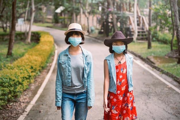Dwie azjatki podróżują w ochronie twarzy w celu zapobiegania koronawirusowi podczas spacerowania w parku