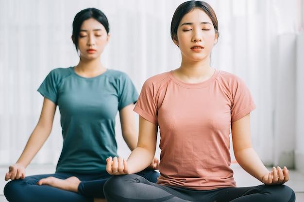 Dwie azjatki praktykują medytację w domu