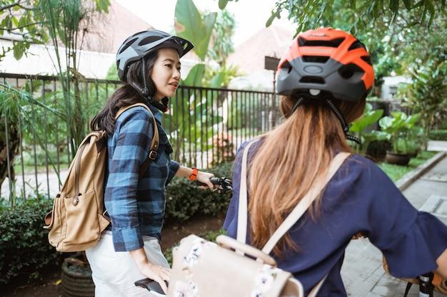 Dwie azjatki rozmawiające i spacerujące podczas spacerów ze składanymi rowerami