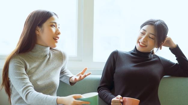 Dwie azjatki rozmawiające przy oknie