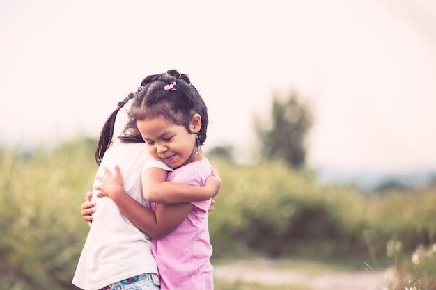 Dwie azjatyckie dziewczynki przytulanie siebie z miłością w tonie kolor vintage
