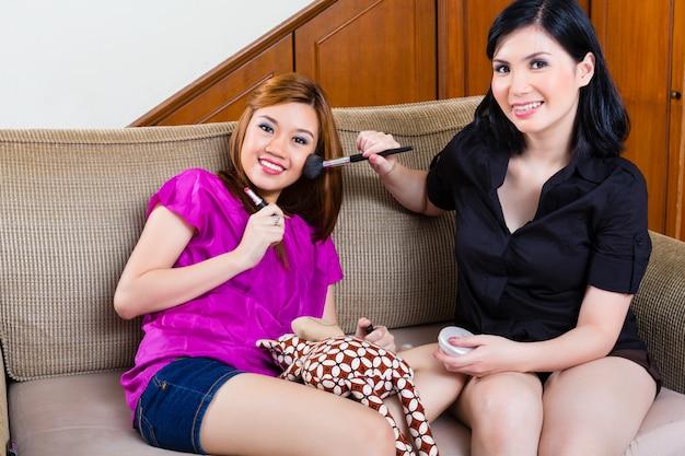 Dwie azjatyckie dziewczyny indonezyjskie domowe za pomocą makijażu
