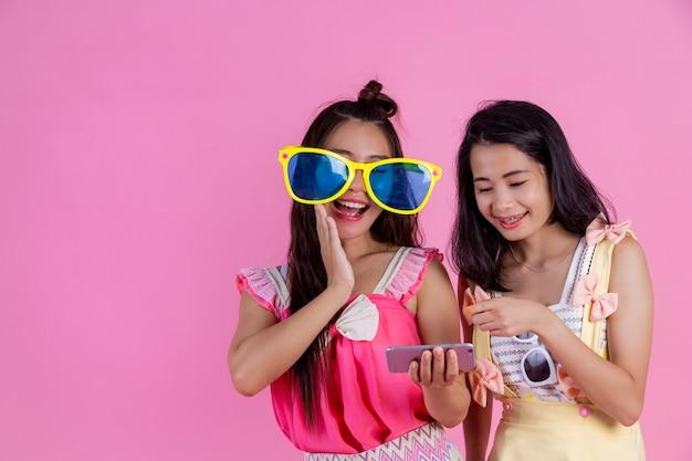 Dwie azjatyckie dziewczyny, które są przyjaciółmi, są szczęśliwe i mają różowe.
