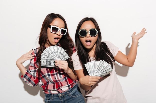 Dwie azjatyckie fajne panie siostry trzyma pieniądze.