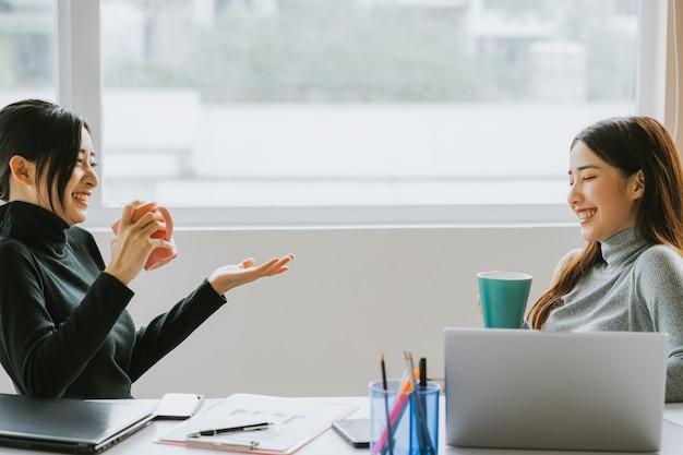 Dwie azjatyckie kobiety biznesu rozmawiające przy oknie podczas przerwy