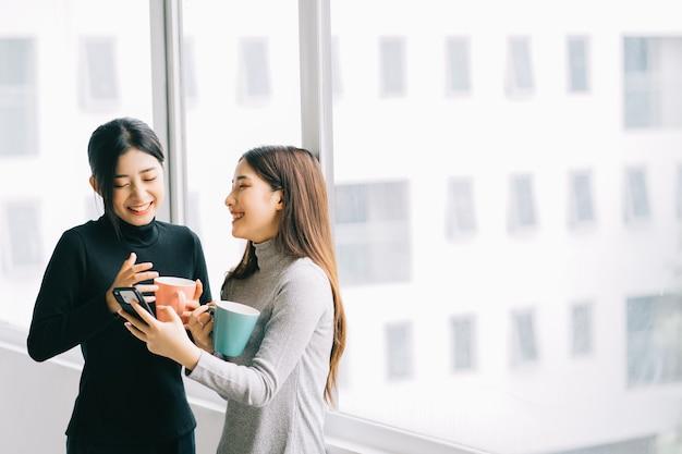 Dwie azjatyckie kobiety biznesu rozmawiały przy oknie podczas przerwy