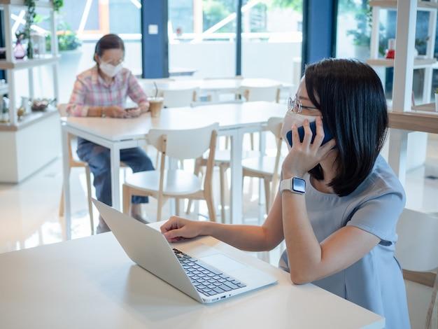 Dwie azjatyckie kobiety noszące maskę i używające smartfona i laptopa do połączenia wideo lub pracy, siedzą na osobnych stołach dla zachowania bezpieczeństwa społecznego dystansowania, jako nowy normalny styl życia.