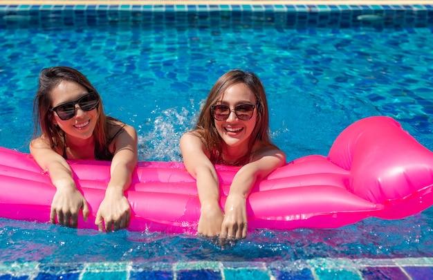 Dwie azjatyckie kobiety relaksujące i leżące na różowych nadmuchiwanych materacach.
