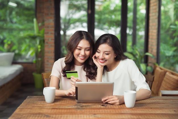 Dwie azjatyckie kobiety używają laptopa do robienia zakupów online z płatnością kartą kredytową
