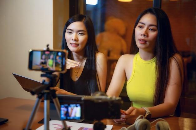 Dwie azjatyckie kobiety vloger nagrywają razem treści wideo na kanał onlinekobieta patrząca na kamerę i rozmawiająca o strzelaniu wideotwórca treści lub koncepcja influencera