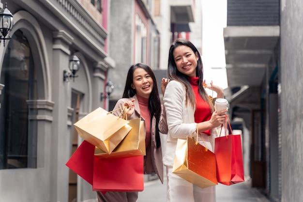 Dwie azjatyckie piękne kobiety z torbami na zakupy w mieście na tle centrum handlowego