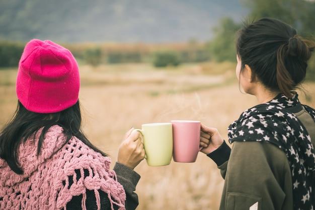Dwie azjatyckie ręce brzęczą gorący kubek kawy na zewnątrz