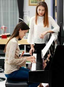 Dwie azjatyckie rodziny, matka i córka uczą się grać na pianinie razem w domu, mama w rozmytym tle