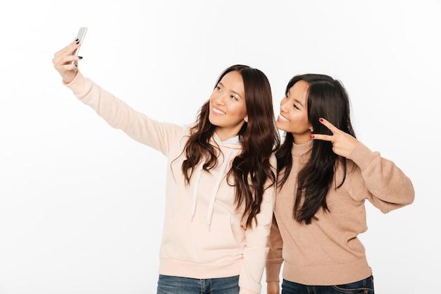 Dwie azjatyckie szczęśliwe pozytywne siostry panie.