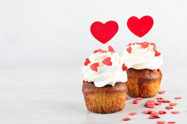 Dwie babeczki z czerwonymi serduszkami na szarym stole, walentynki, słodki prezent