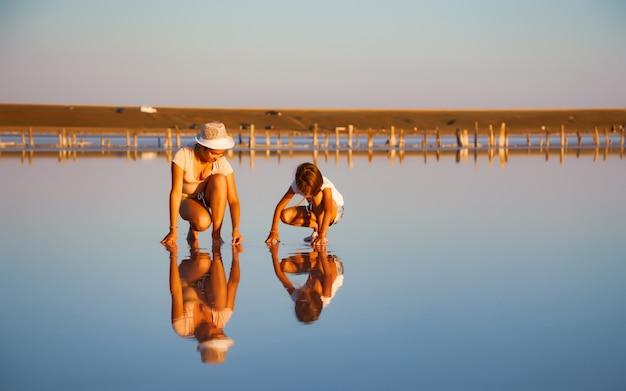 Dwie bajecznie piękne dziewczyny w niecodziennych strojach na przepięknym przejrzystym słonym jeziorze szukają czegoś na błyszczącej powierzchni