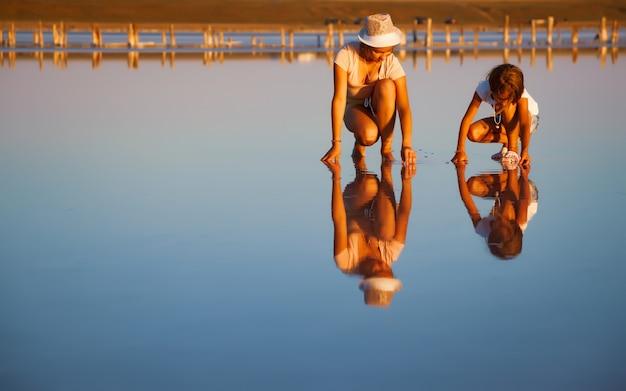 Dwie bajecznie piękne dziewczyny w niezwykłych strojach na pięknym przezroczystym słonym jeziorze szukają czegoś na błyszczącej powierzchni