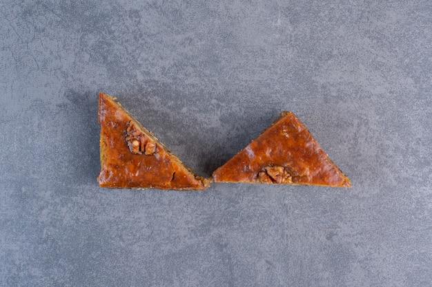 Dwie baklawy z ziarnami orzecha włoskiego na marmurowym stole.
