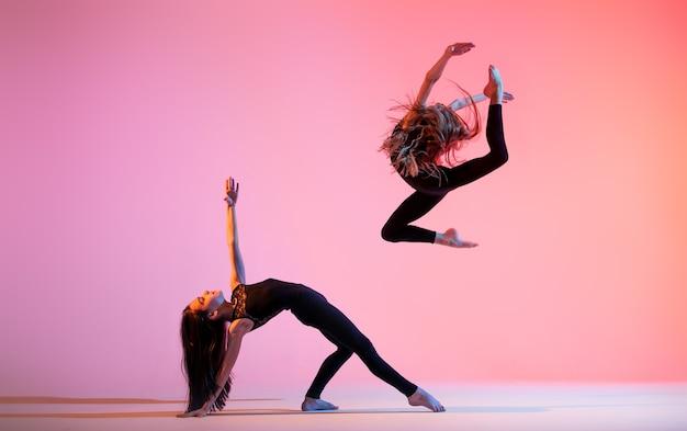 Dwie baletki z długimi luźnymi włosami w czarnych obcisłych garniturach tańczą na czerwonym tle