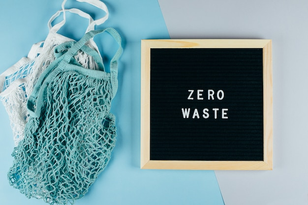 Dwie bawełniane torby wielokrotnego użytku (torby siatkowe) i tablica z tekstem zero waste