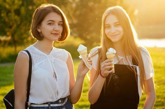 Dwie beautifu najlepsze dziewczyny uczennice (uczennica) jedzą lody w rogu waflowym w parku