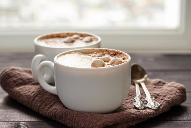 Dwie białe filiżanki cappuccino z piankami i łyżkami na drewnianym stole. zamknij się zdjęcie z selektywną ostrością