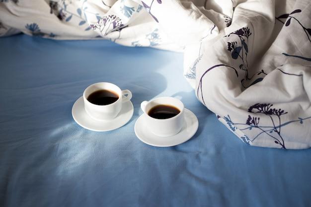 Dwie białe filiżanki kawy są w łóżku, słoneczny poranek