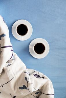 Dwie białe filiżanki kawy są w łóżku