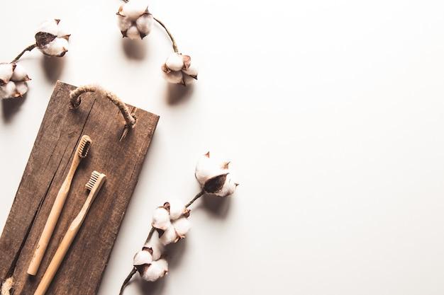 Dwie białe i żółte ekologiczne szczoteczki do zębów drewniane bambusowe na drewnianym tle z białym. plastikowy symbol zrównoważonego stylu życia