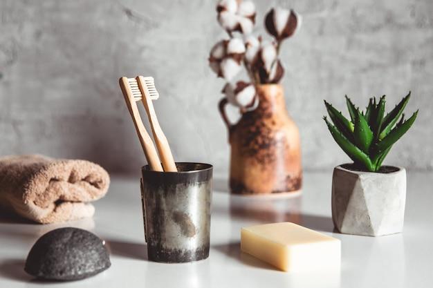 Dwie białe i żółte ekologiczne szczoteczki do zębów z bambusa na drewnianym stole
