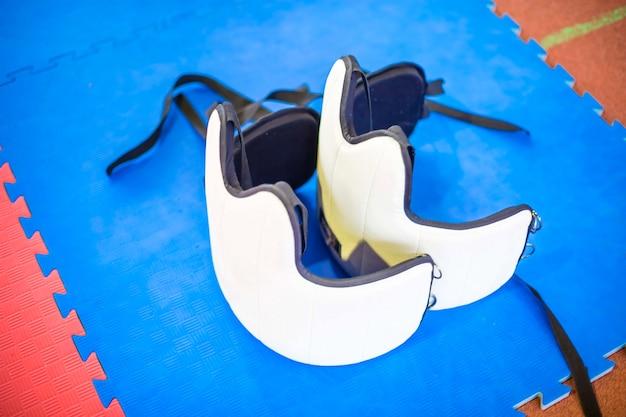 Dwie białe kamizelki ochronne do sztuk walki na niebieskiej podłodze sprzęt do ochrony karate