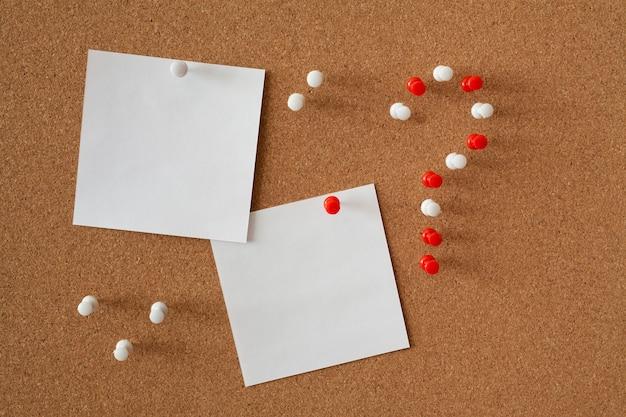Dwie białe kartki papieru na notatki na tablicy korkowej. znak zapytania składa się z czerwonych i białych szpilek. pomysł na biznes.