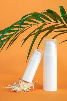 Dwie białe puste butelki po kosmetykach z filtrem przeciwsłonecznym, kremem do opalania lub innym produktem kosmetycznym, muszlą i palmą