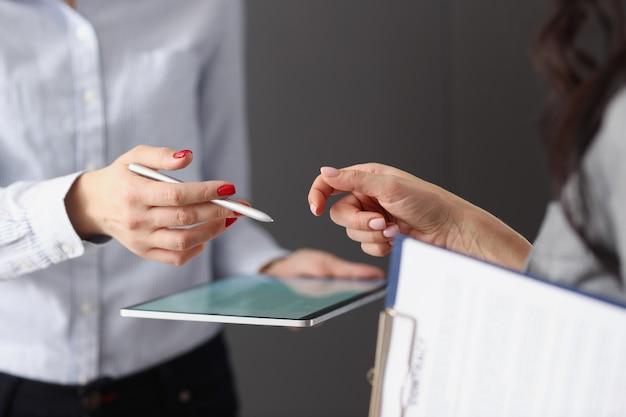 Dwie bizneswoman rozmawiająca i trzymająca tablet i dokumenty aplikacje mobilne dla biznesu