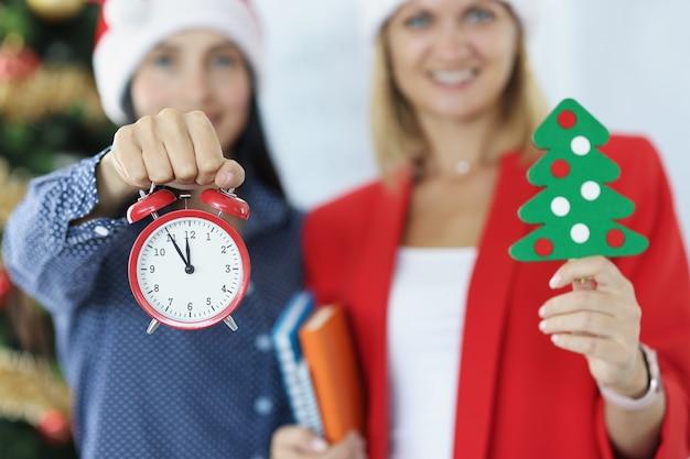 Dwie bizneswoman trzyma czerwony budzik i choinkę nowy rok i święta bożego narodzenia