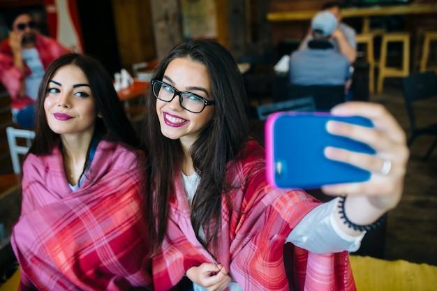 Dwie bliskie koleżanki chcą zrobić sobie selfie w kawiarni z pamięci