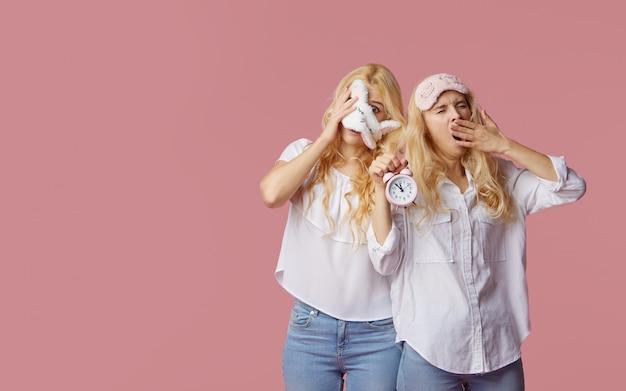 Dwie bliźniaczki bezsenne młode kobiety w piżamie i maseczkach na różowej ścianie. budzik obudził kobiety