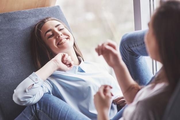 Dwie bliźniaczki siedzą dla nich w ciasnym fotelu w strefie rekreacyjnej. siostry pozują i dobrze się bawią. zawsze dołącz do koncepcji przyjaźni i młodości