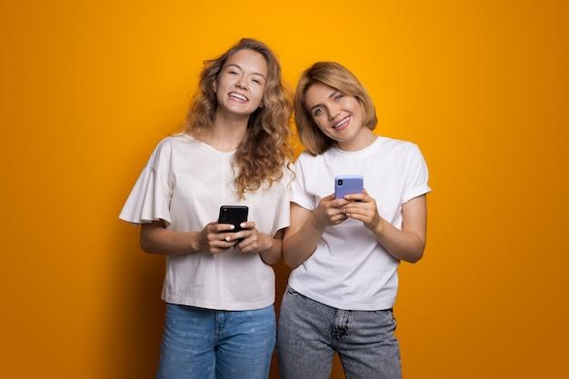 Dwie blond słodkie kobiety na czacie na telefon komórkowy o uśmiecha się do kamery