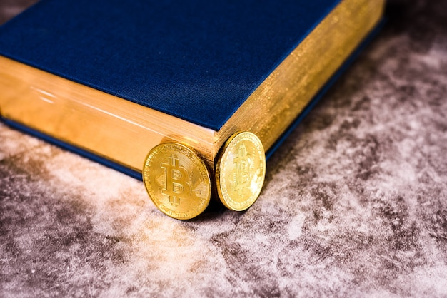 Dwie błyszczące złote monety bitcoin obok książki o tajemnicach bogactwa.