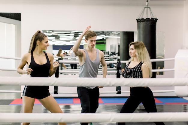 Dwie bokserki witają się przed walką, między nimi stoi młody przystojny trener. boksować ludzi