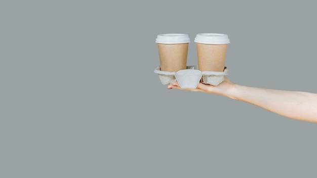 Dwie brązowe jednorazowe filiżanki do kawy na kartonowym stojaku