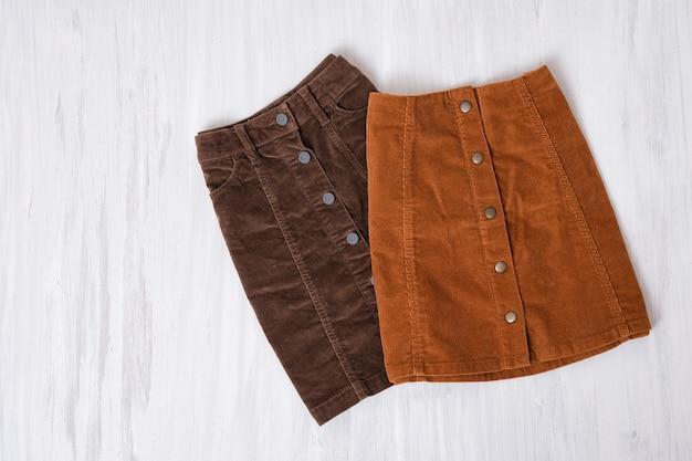 Dwie brązowe spódnice na drewnianej powierzchni