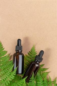 Dwie brązowe szklane butelki z serum, olejkiem eterycznym lub innym produktem kosmetycznym i zielonymi liśćmi paproci na tle rzemiosła